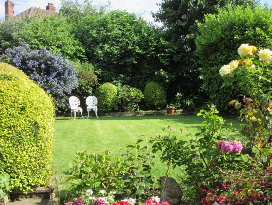 Un beau jardin avec de la pelouse et des rosiers en premier plan